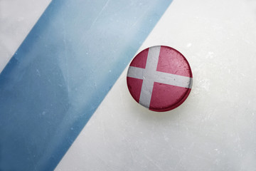 old hockey puck with the national flag of denmark