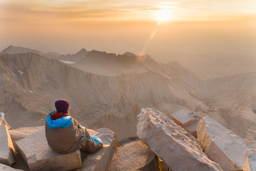 A young woman wearing a warm hat and wrapped in a sleeping bag sits on the edge of a cliff and watches the sunrise in the High Sierra