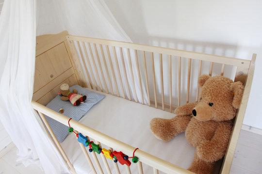 Ein Teddybär sitzt in einem Kinderbett
