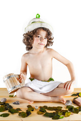 Cute curly-haired boy shirtless in a towel is sitting cross-legged with a wooden mug in hand, smiling, looking into the camera. Background bleached wood.