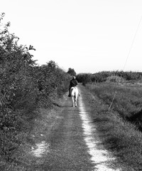 black and white photo of man riding his horse in a meadow