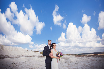 Bride and groom on clouds background