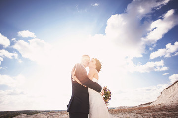 Toned photo of bride and groom on sunset. Happy wedding concept