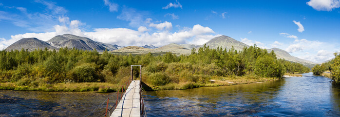 creak in rondane national park in norway with suspension bridge