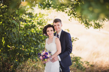 Happy newlyweds looking to camera, portrait of beautiful bride and groom