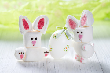 Funny marshmallow rabbits with Easter egg, sweet bunnies on a green background