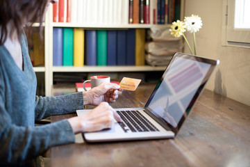 woman with green sweater typing in portable laptop paying online with made up credit card on wooden table at home