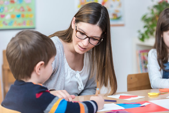 Kindergarten Teacher Supports Child on Class