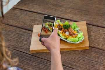 Photographer clicking a picture of food using smartphone