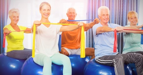 Portrait of seniors using exercise ball and stretching bands
