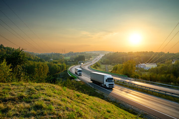 Fotobehang - White trucks driving on the highway winding through forested landscape at sunset.