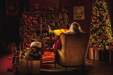 A view from behind of Santa working at his desk in a Christmas-decorated room