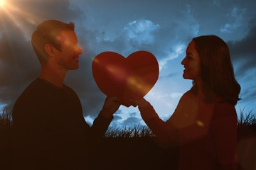 Composite image of smiling couple holding red heart shape