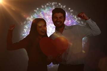 Composite image of cheerful couple holding paper heart