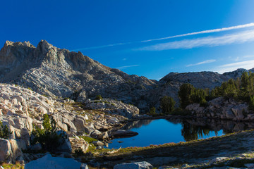 Solitary alpine lake sits under tall granite mountains in the late afternoon sunlight in the high sierra