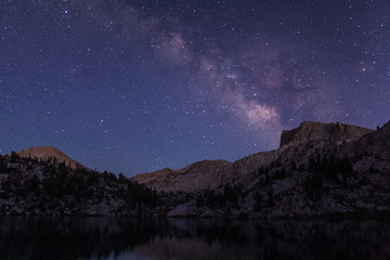 Milky way rises over a granite bluff at the Lake of the Lone Indian in the high sierra