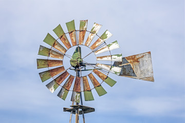 Rusty Green Windmill and Cloudy Blue Sky