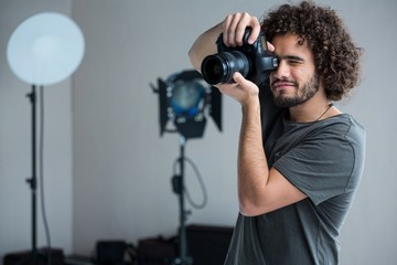 Happy male photographer with digital camera in studio