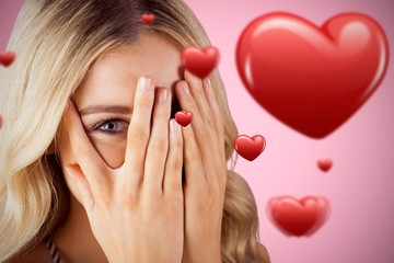 Composite image of beautiful blonde woman hiding behind hands