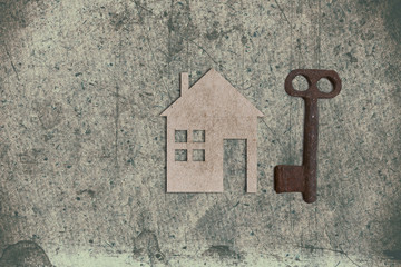 model of cardboard house with key on old textured paper backgrou