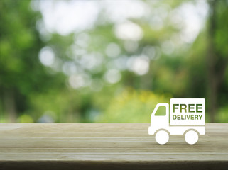 Free delivery truck icon on wooden table over blur green tree background, Transportation business concept