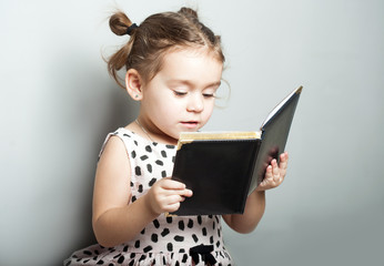 Cute little girl reading book on grey background in pink dress