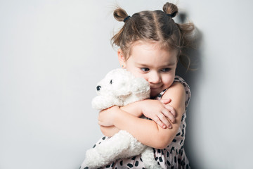 Cute little girl in pink dress huggin toy puppy on grey background