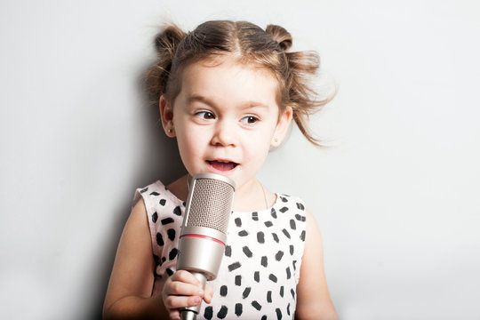 Happy Cute little girl singing a song on microphone. Grey background