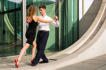 two young people - a man in white shirt and a woman wearing black dress - dancing tango outside somewhere in the city near modern buildings