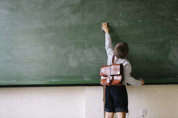 A kid cleaning the blackboard