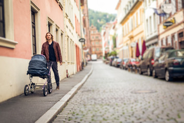 Young Father With Baby Stroller In The City