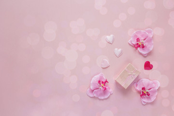 Background with gift box, orchid flowers and hearts on a pink.