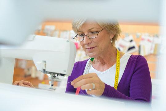 View through sewing machine of senior seamstress