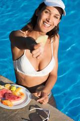 femme souriante en maillot de bain au bord d'une piscine avec une assiette de fruits