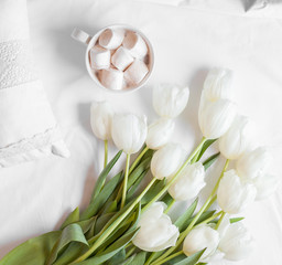Spring flowers tulips with cacao and white pillows