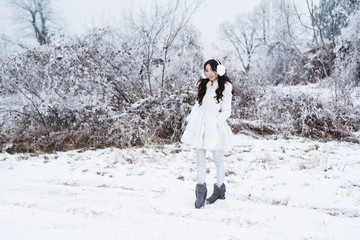 Young beautiful happy girl walking in park. Model wearing stylish winter clothing. Outdoor active fun.