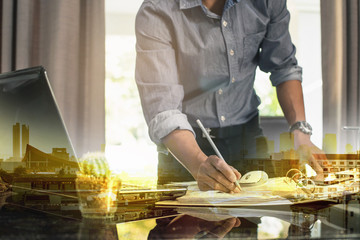 business documents on office table with smart phone and book and laptop computer and man working in the city background