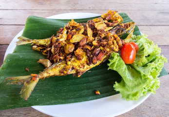 Thai Traditional Style Fried Fishes with Herbs like Turmeric and Garlic Served on Banana Leaf with Tomato and Cabbage. Healthy Food for Diet.