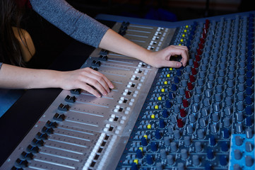 An expert adjusting audio mixing console