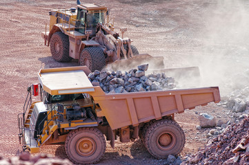 View into a quarry mine. earth mover loading dumper truck with r