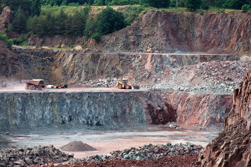 View into a quarry mine with dumper truck and earthmover