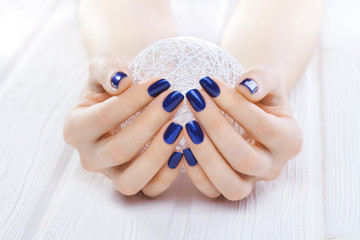 blue manicure with a white ball of yarn