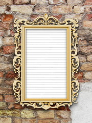 Golden Baroque picture frame with striped paper on old weathered brick wall background