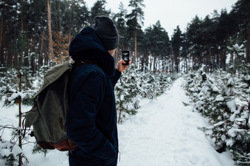 Traveler takes selfie of snowy landscape in winter forest on mobile phone