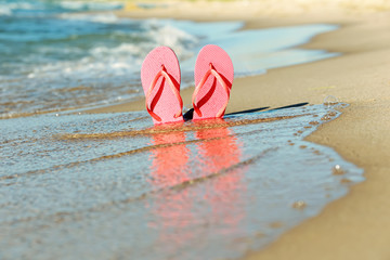 Pink flip flops in the sand on the beach