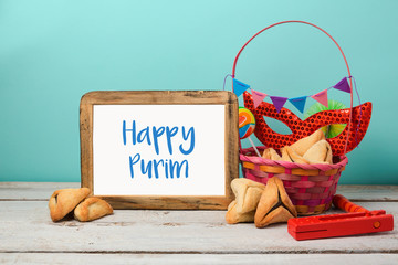 Jewish holiday Purim concept with hamantaschen cookies or hamans ears and carnival mask with photo frame mock up.