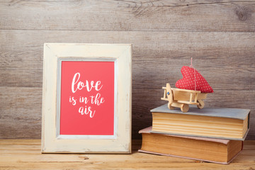 Valentines day concept with toy airplane, heart shape and photo frame over wooden background