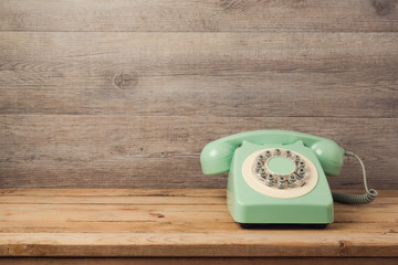 Retro telephone on wooden table. Call center or support service concept background
