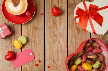 Valentines day concept with macarons, coffee cup and gift box over wooden background. Top view from above