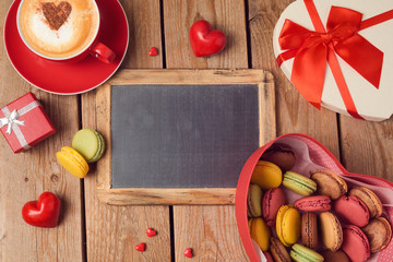Valentines day concept with macarons, coffee cup and chalkboard over wooden background. Top view from above